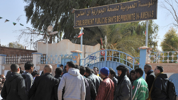 People gather Friday outside a hospital in eastern Algeria as they try to get information on those wounded during a military raid on a gas plant where Islamic extremists were holding hostages. (AP)
