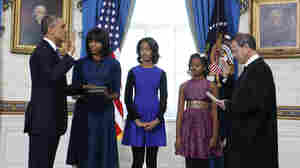 President Obama is officially sworn in Sunday by Chief Justice John Roberts in the Blue Room of the White House. Next to Obama are first lady Michelle Obama, holding the Robinson Family Bible, and their daughters, Malia and Sasha.