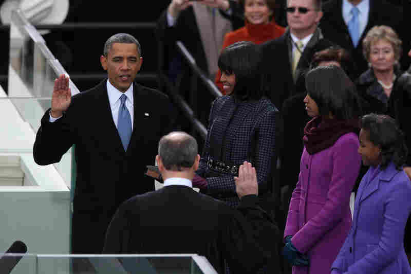 Obama is sworn in by Chief Justice John Roberts as Michelle and their daughters, Malia and Sasha, look on.