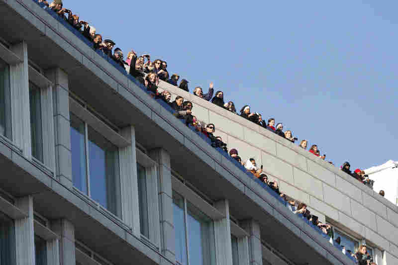 Spectators watch from rooftops as the presidential limousine heads to the White House.
