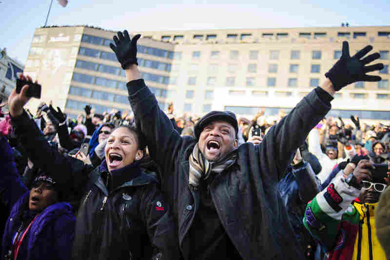 Spectators wave to Obama as the inaugural parade moves down Pennsylvania Avenue.