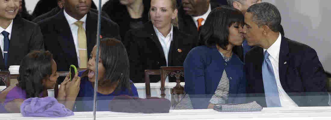 President Barack Obama kisses first lady Michelle Obama as their daughters Sasha, left, and Malia, second from left, look on during the Inaugural parade.