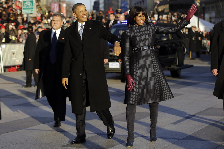 Obama and Michelle walk in the inauguration parade near the White House. The first lady chose a coat by designer Thom Browne. (AP)