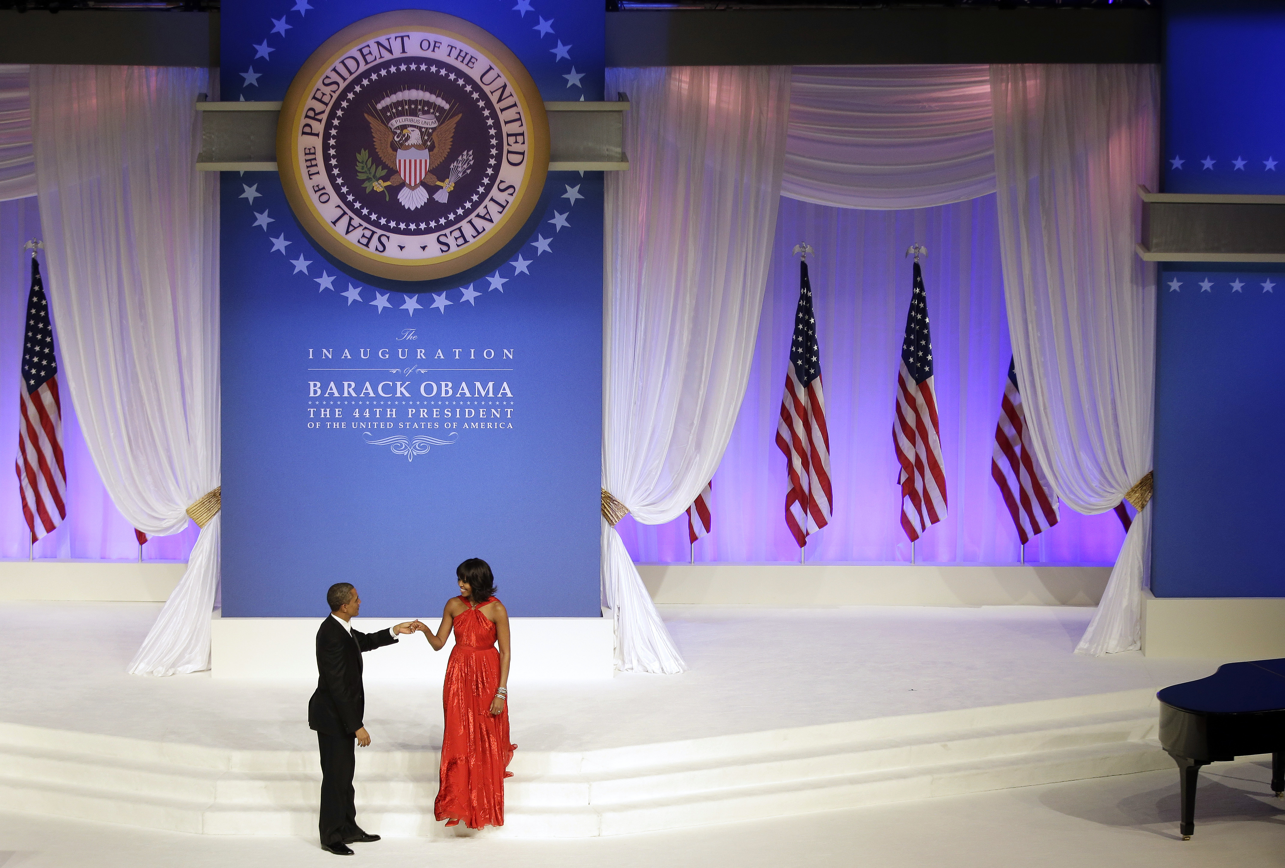 President Obama greets first lady Michelle Obama on stage during the Commander-In-Chief inaugural ball. Michelle's dress was designed by Jason Wu.