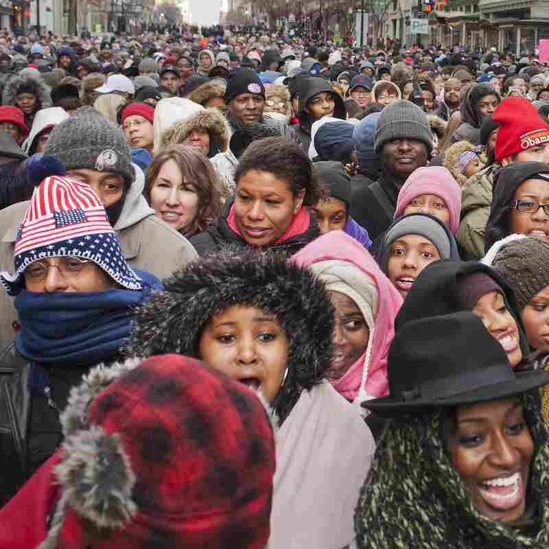 A crowd walks through downtown Washington, D.C., toward the National Mall.