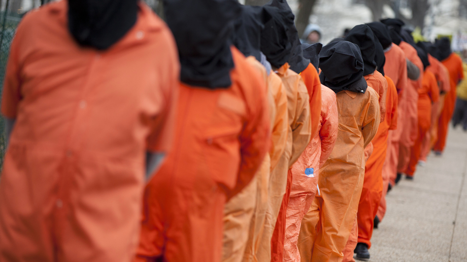 Demonstrators, dressed as detainees, march on Jan. 11 against the U.S. military detention facility in Guantanamo Bay, Cuba, and call for President Obama to close the facility. (AP)