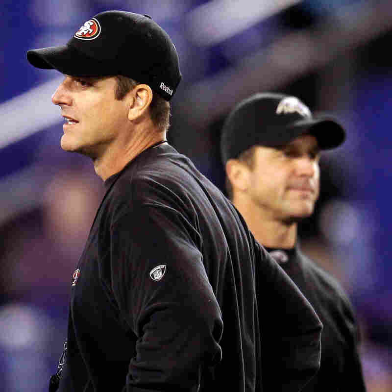 Head coach Jim Harbaugh (left) of the San Francisco 49ers and his brother, head coach John Harbaugh of the Baltimore Ravens, before a game on Thanksgiving Day 2011. Their teams will meet again in the Super Bowl.