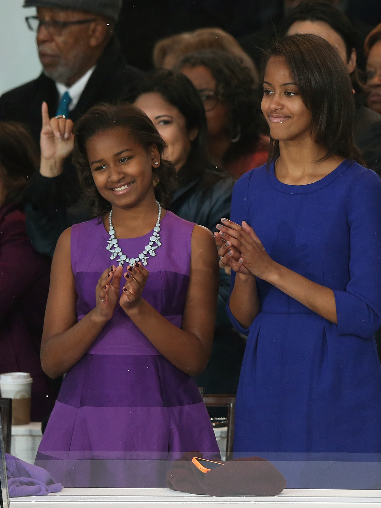 Sasha and Malia Obama clap  from the reviewing stand in the nation's capital as they watch the presidential inaugural parade.