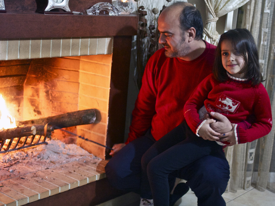 Sotiris Sotiriou, 41, and his daughter Sophia, 5, check out the olive-wood kindling in the fireplace that heats their family's home. (NPR)