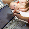 Patient William Wishart, age 4 months, looks on as Dr. Melanie Walker uses a portable computer to enter information from his exam into an electronic medical records system, in North Raleigh, N.C., in November.