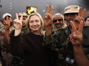 Secretary of State Hillary Clinton stands with Libyan fighters who ousted Moammar Gadhafi during an Oct. 18, 2011, visit to Libya. Clinton was a strong supporter of U.S. intervention in Libya.