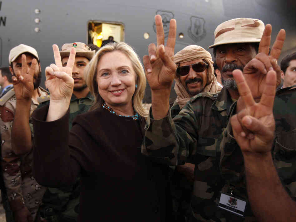 Secretary of State Hillary Clinton stands with Libyan fighters who ousted Moammar Gadhafi during an Oct. 18, 2011, visit to Libya. Clinton was a strong supporter of U.S. intervention in Lib
