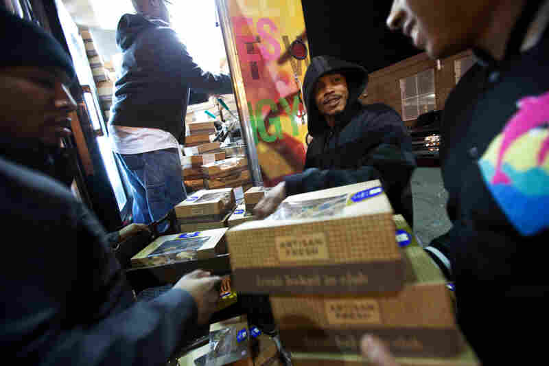 Albert Lebron (center) helps friends stuff almost 250 muffin boxes into the Capital Chicken and Waffle Food Truck the night before the inauguration celebrations. This was the first time that many food trucks were permitted along the parade route. Due to security measures each truck was only allowed to carry whatever food could be packed into the truck that morning.