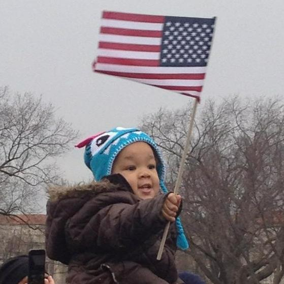 "Standing among the crowd at the inaugural parade, All Things Considered Host Melissa Block snapped this photo of two-year-old Taniya Washington hoisted on her uncle's shoulders with an American flag. According to Block's tweet, Taniya's uncle told his nieces, ""Y'all's next! You guys are the future!"""