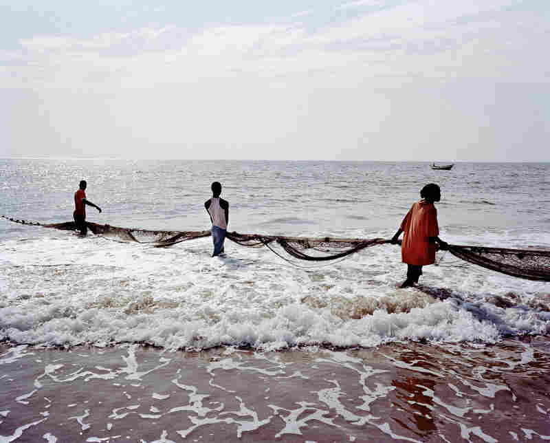 Fishermen drag in a net at Lumley Beach in west Freetown. The polluted waters often bring small amounts of fish, tangled together with bottles and other trash.