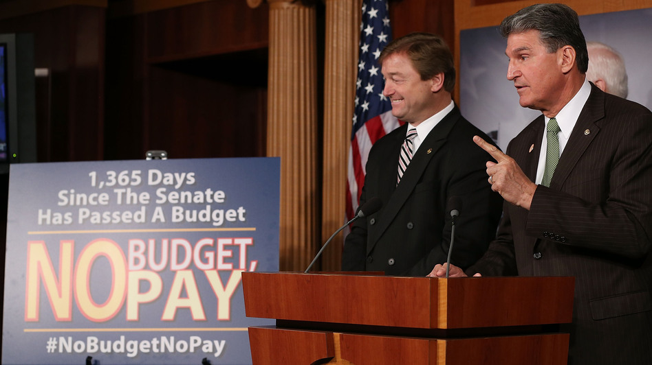 Sen. Dean Heller (left), R-Nev., and Sen. Joe Manchin, D-W.Va., speak Wednesday at the U.S. Capitol about legislation to delay a potential clash over the debt ceiling until May — and to freeze the paychecks of lawmakers if they don't pass a budget resolution. (Getty Images)