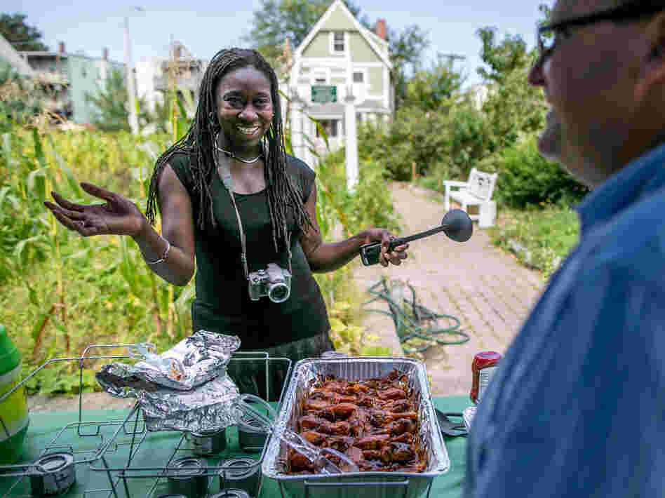 Jhana Senxian, head of the Coleman Street Association, serves food during a block party.
