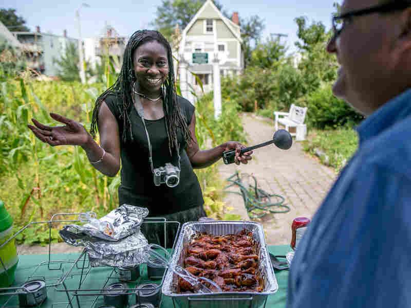 Jhana Senxian, head of the Coleman Street Association, serves food during a block party.