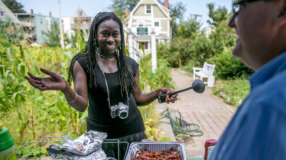 Jhana Senxian, head of the Coleman Street Association, serves food during a block party. (The Boston Globe)