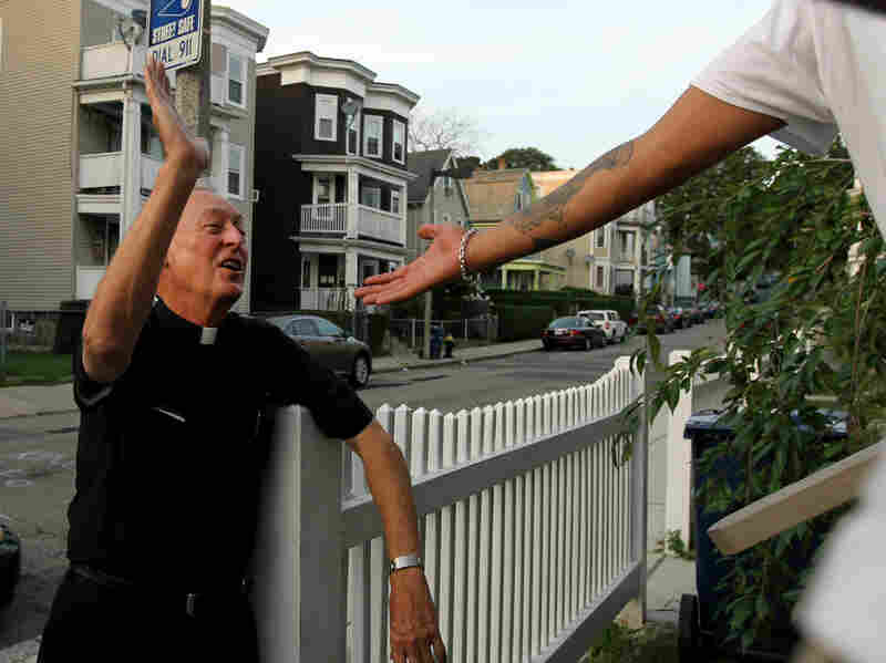 """Father Richard """"Doc"""" Conway, of St. Peter Church, high-fives a man while walking the neighborhood on a Friday night."""