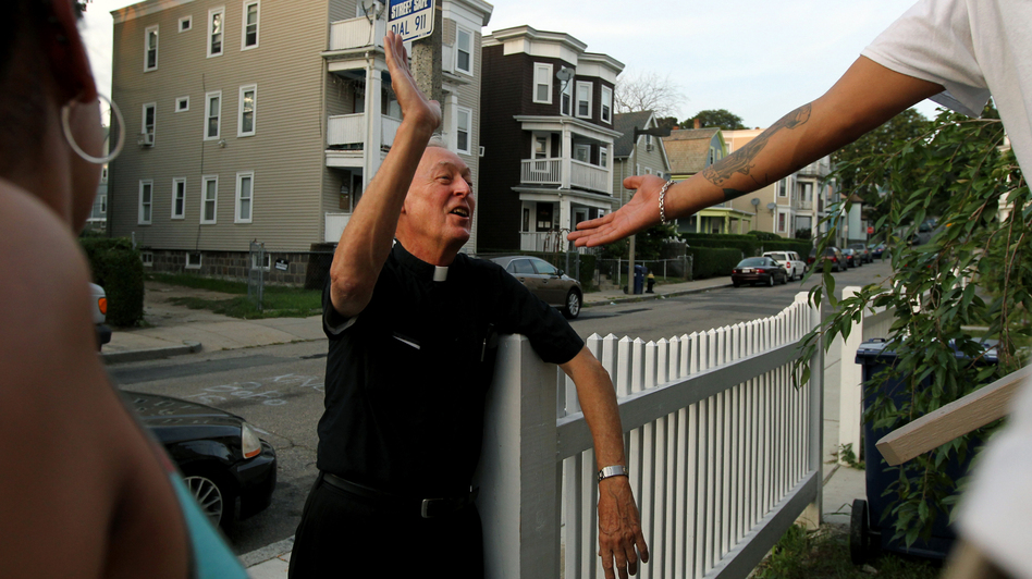 "Father Richard ""Doc"" Conway, of St. Peter Church, high-fives a man while walking the neighborhood on a Friday night. (The Boston Globe)"