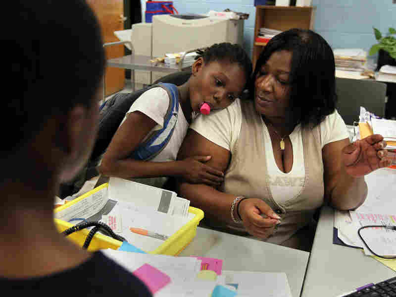 Theresa Johnson gets a hug from first-grader Shaundene Funches on the last day of the year at Marshall Elementary School in Dorchester, Mass.