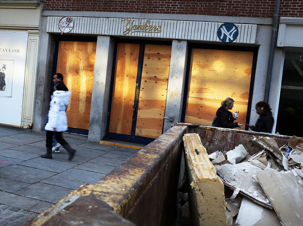 People walk past a closed business affected by Hurricane Sandy in the heavily damaged South Street Seaport in New York City in December.