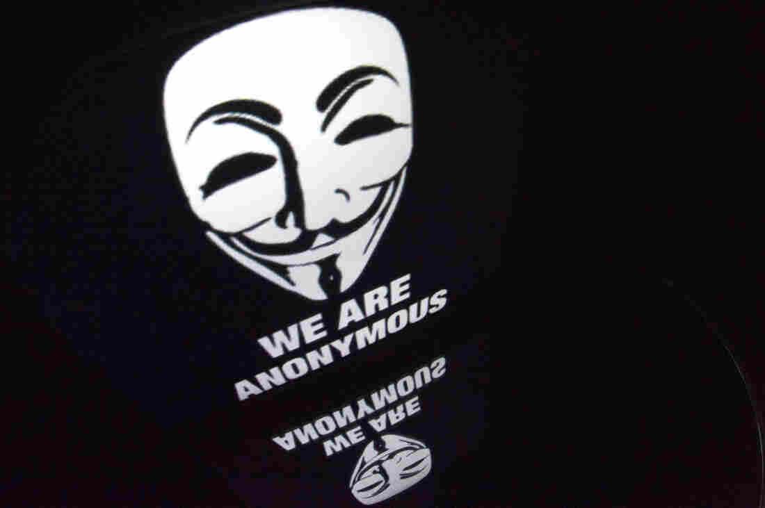 """The """"Anonymous"""" logo is seen on a tablet screen."""