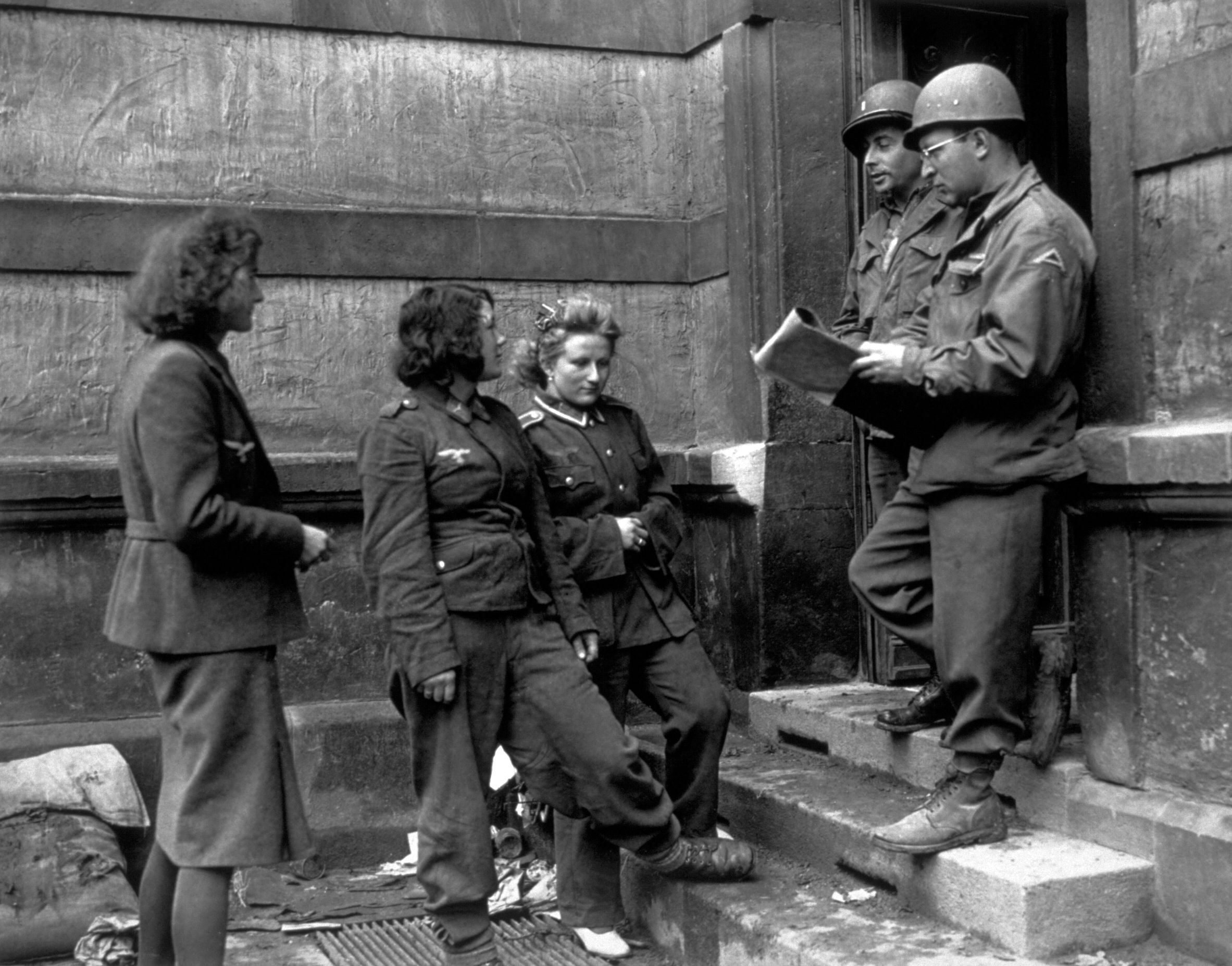 Female German army prisoners being checked in by German-speaking Americans at a German Women's Detention Building in 1945. The women were captured at the front on the 7th U.S. Army sector.