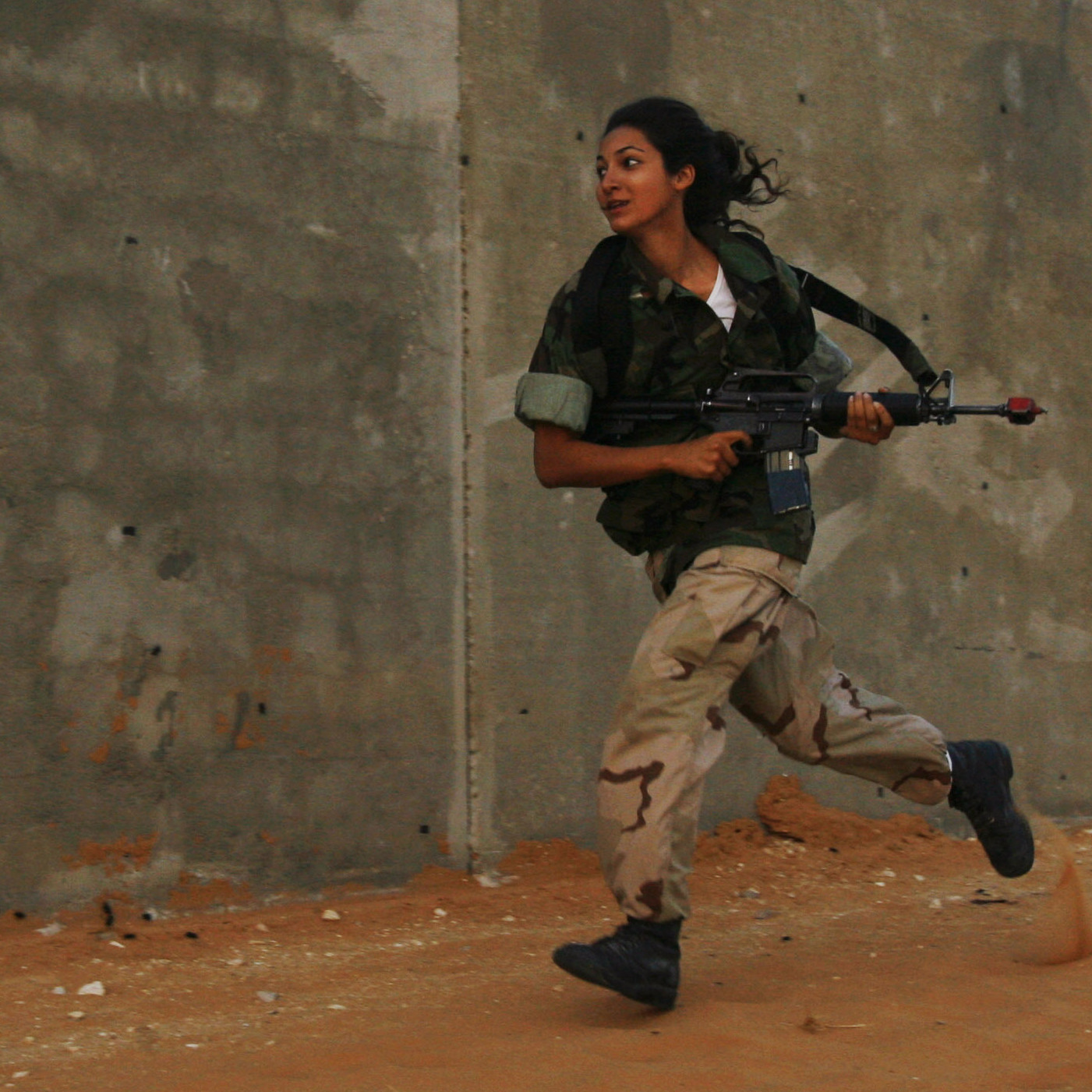 A female Israeli soldier runs during an urban warfare exercise at an army training facility, near Zeelim, Israel on June 19, 2008.