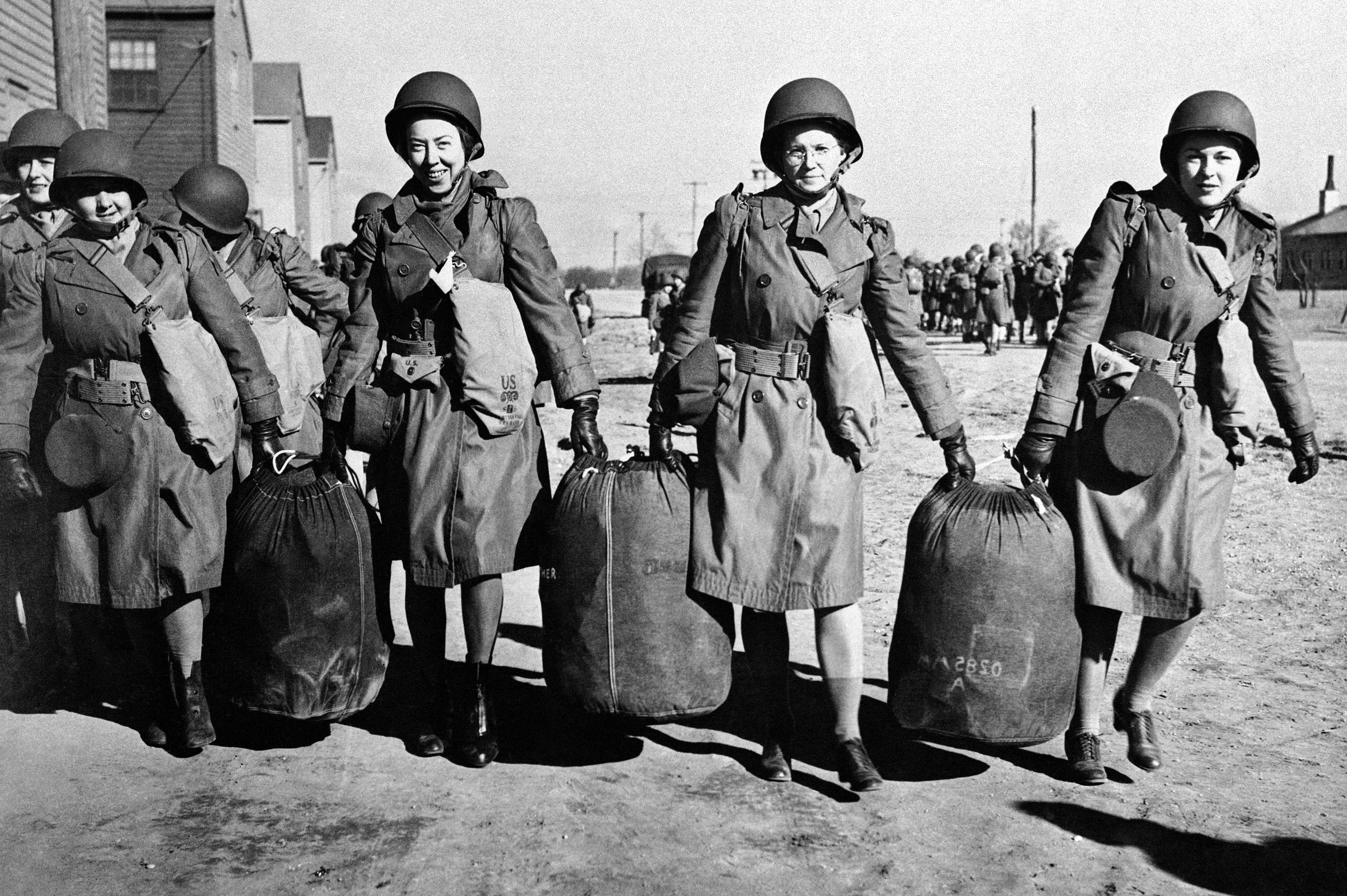 Women help each other with bags at an embarkation port in the U.S. in this Jan. 29, 1943, photo provided by the U.S. Army. They were bound for North Africa with the first detachment of the Women'�s Auxiliary Army Corps to be sent abroad.