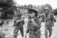 A female Cambodian soldier totes a machine gun into combat during an operation across the Mekong River from Phnom Penh in the Prek Tamak area of Cambodia on Aug. 26, 1970. This region was the scene of heavy fighting between Cambodian troops and Viet Cong. The young woman is one of many who served as regular soldiers and medics in the rapidly expanded army .