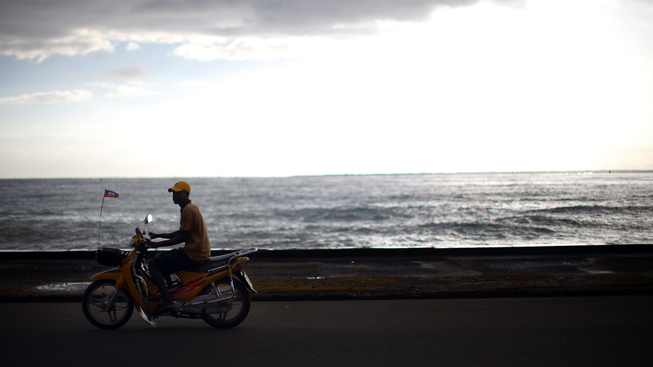 A motorcyclist rides along the main promenade in Cap-Haitien next to the harbor and the bay. Haiti has miles of undeveloped beaches and coastline that tourism officials say should be used to attract foreign investment. (NPR)