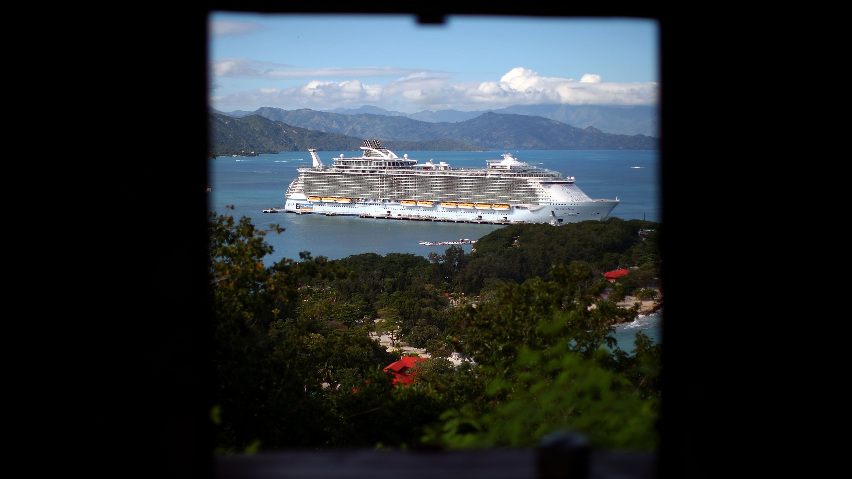 The Allure of the Seas is the newest ship in the Royal Caribbean fleet and the largest cruise ship ever built. It sits at a pier at Labadee on the coast of northern Haiti. Guests go ashore to an enclosed private beach.