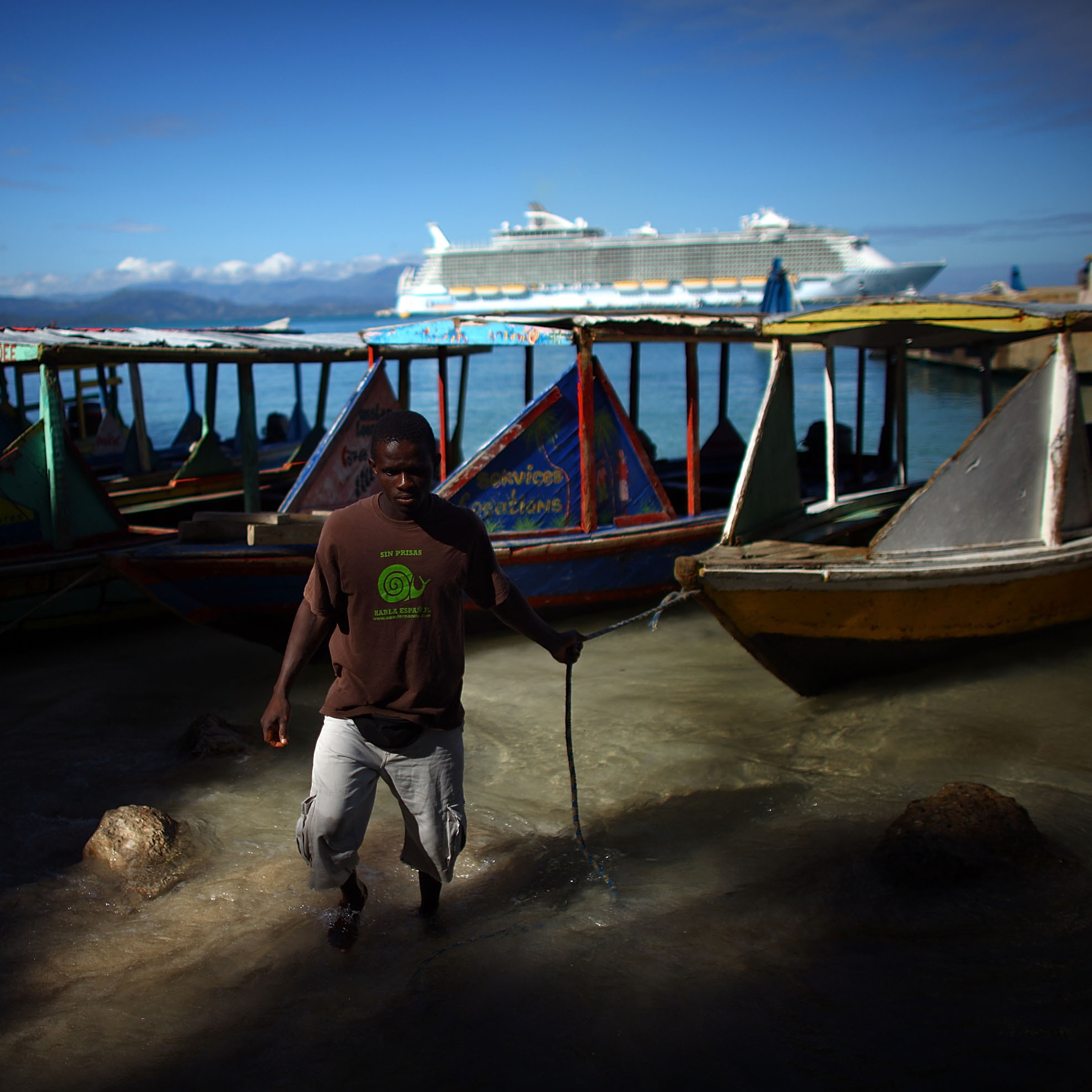 The Royal Caribbean Allure of the Seas sits behind the fishing boats and water taxis near the village of Labadee in northern Haiti. Guests of the cruise ship come ashore but are not allowed beyond a fence that separates the locals from the tourists.