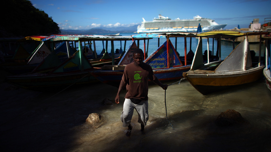 The Royal Caribbean Allure of the Seas sits behind the fishing boats and water taxis near the village of Labadee in northern Haiti. Guests of the cruise ship come ashore but are not allowed beyond a fence that separates the locals from the tourists. (NPR)