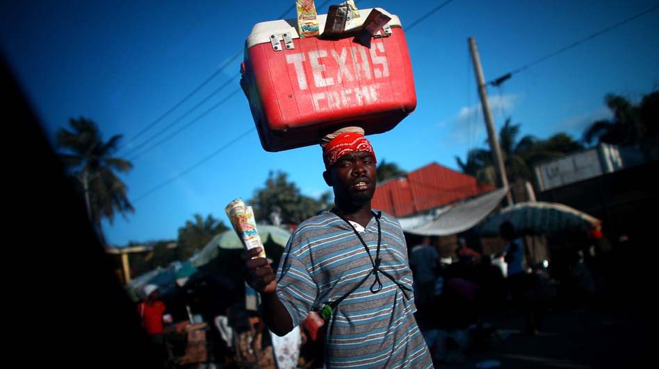Street vendors peddle cool drinks to drivers stuck in one of the daily traffic jams on Highway 1, which is the main route out of Port-au-Prince, the Haitian capital, to the north. Traffic is one of the obstacles to tourism development in the impoverished Caribbean nation. (NPR)