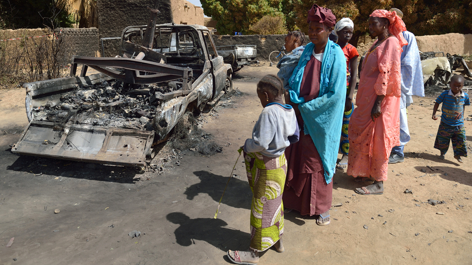 Malians gather around the remains of vehicles used by Islamist rebels that were destroyed by an earlier French airstrike, Jan. 23 in Diabaly, about 250 miles north of Bamako, Mali's capital. (AFP/Getty Images)