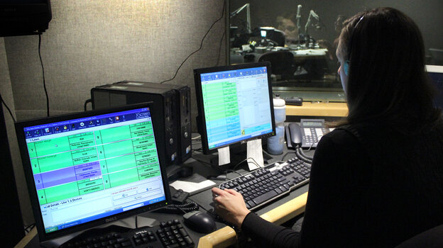 NPR Editorial Assistant Laura Lee takes and screens calls during a live broadcast of Talk of the Nation. Look just above Lee's head to see Neal Conan in the hosting chair on the other side of the glass.