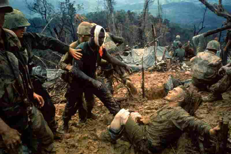 Wounded Marine Gunnery Sgt. Jeremiah Purdie (center, with bandaged head) reaches toward a stricken comrade after a fierce firefight south of the Demilitarized Zone in Vietnam, October 1966.