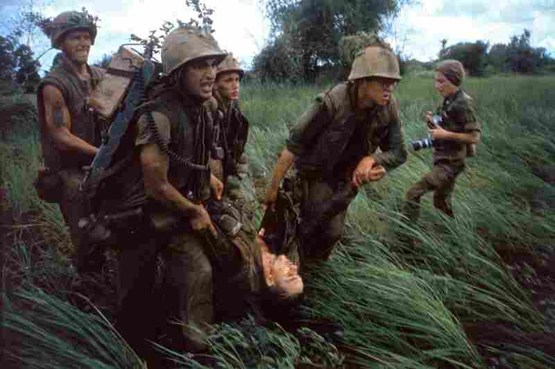 "Four Marines recover the body of a fifth as their company comes under fire near Hill 484 in Vietnam, October 1966. At right is the French-born photojournalist Catherine Leroy (1945 -€"" 2006); she was cropped out of the version of this photo that originally ran in Life."