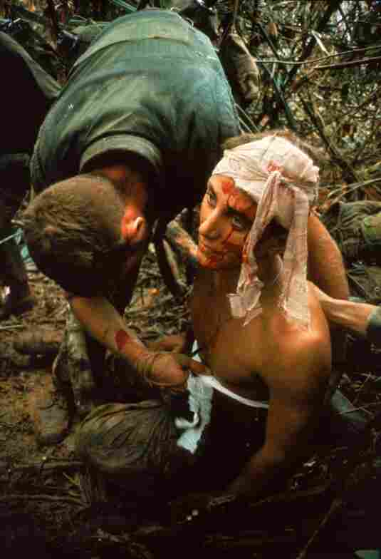A dazed, wounded American Marine gets bandaged during Operation Prairie near the Demilitarized Zone during the Vietnam War, October 1966.
