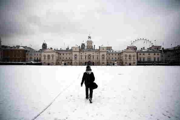 A man walks across a snowy Horse Guards Parade in London, England.