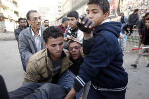 Egyptians carry a wounded protestor during clashes with riot police in Tahrir Square on January 25, 2013.