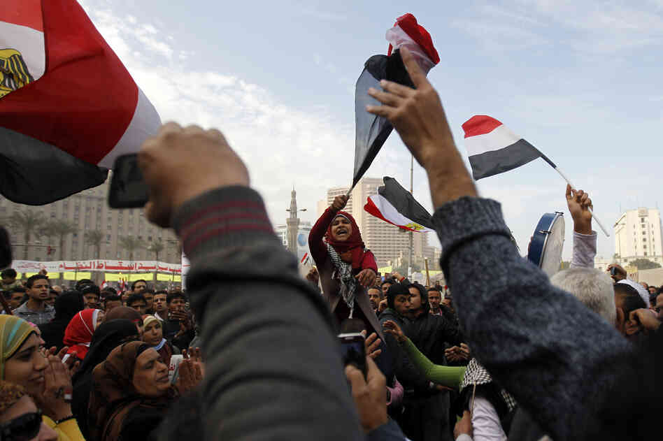 Egyptian demonstrators wave the national flag and shout slogans during a protest in Tahrir Square on January 25, 2013 in Cairo.