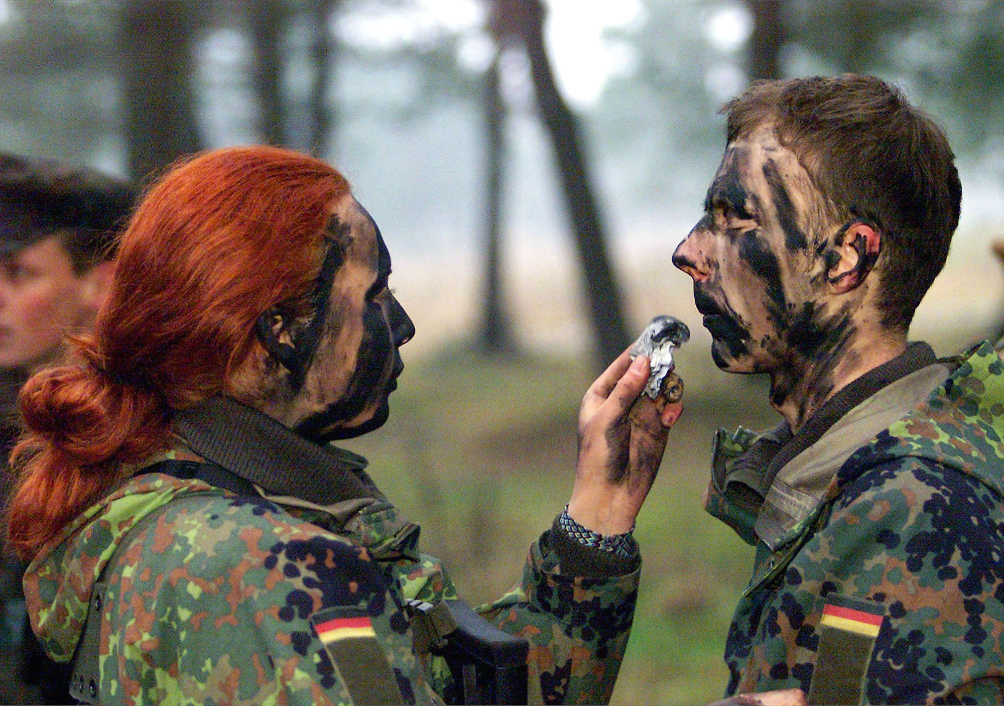 Private Dajana Bartczewski (left) puts camouflage paint on the face of a male soldier during an exercise by German Bundeswehr soldiers from the barracks in Augustdorf, western Germany, on Jan. 9, 2001.