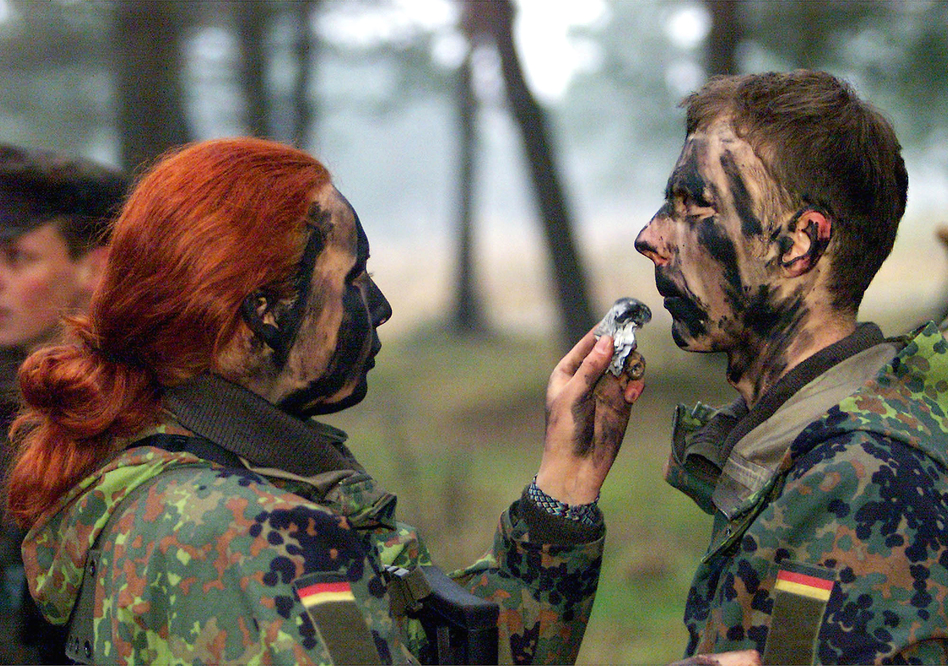 Private Dajana Bartczewski (left) puts camouflage paint on the face of a male soldier during an exercise by German Bundeswehr soldiers from the barracks in Augustdorf, western Germany, on Jan. 9, 2001. (AP)