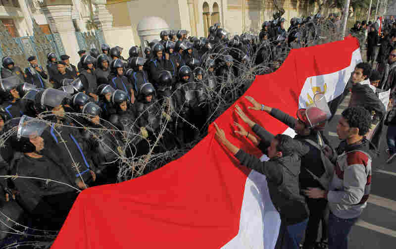 Egyptian protesters hang a giant banner in the colors of Egypt's national flag on barbed wires in front of anti-riot soldiers at the entrance to the presidential palace in Cairo, Egypt, Friday, Jan. 25, 2013.