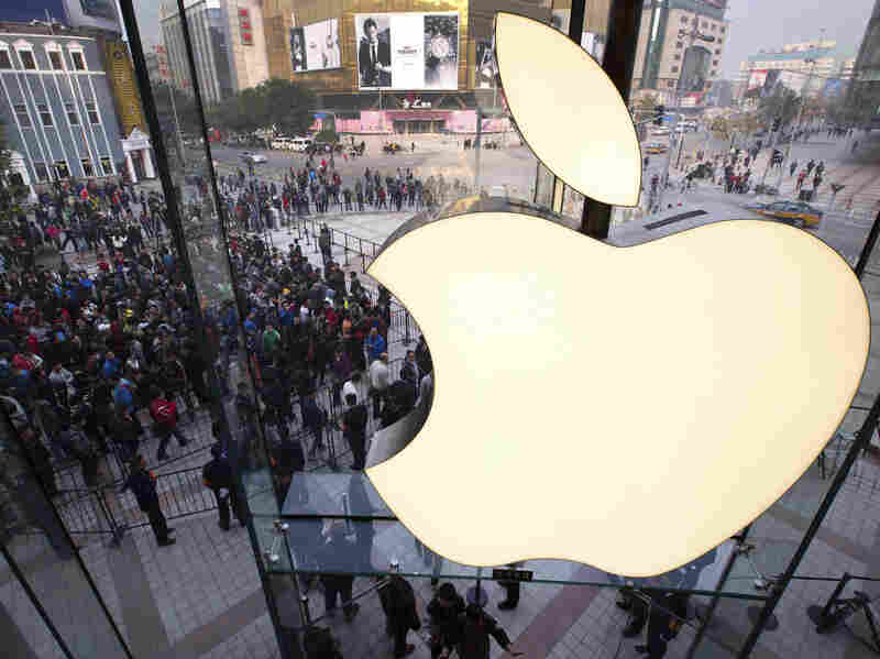 In this Oct. 20, 2012 photo, people line up to enter a newly opened Apple Store in Beijing. Exxon has once again surpassed Apple as the world's most valuable company after the iPhone and iPad maker saw its stock price falter.