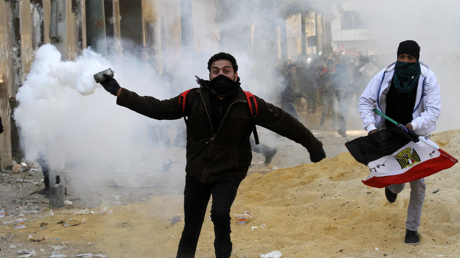 An Egyptian protester runs to throw tear gas during a protest in Tahrir Square on January 25, 2013 in Cairo. (AFP/Getty Images)